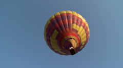 Red-yellow balloon flying in cloudless sky Stock Footage