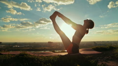 Woman doing yoga in floating boat pose in the park at sunset Stock Footage