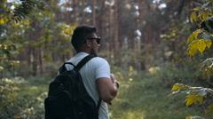 Tourist enjoying fresh air while resting after strolling in forest in sunny Stock Footage