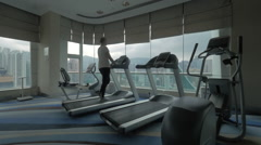 Clip of woman on the treadmill in fitness centre looking at window with Stock Footage