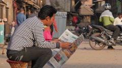 Man reading newspaper on street,Bhaktapur,Nepal Stock Footage