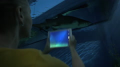 Woman with pad taking shot of sea animal in oceanarium Stock Footage