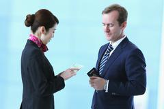 Japanese attractive flight attendant helping customer at the airport Stock Photos