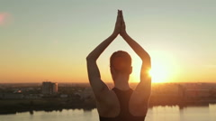 Sporty woman practicing yoga in the park at sunset - sun salutation Stock Footage