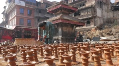 Woman putting pottery candles on square for drying in sun,Bhaktapur,Nepal Stock Footage
