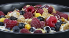 Cereal flakes muesli with blueberries, raspberries and sea buckthorn rotating Stock Footage