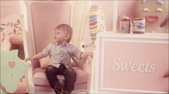 Cute one year old baby sitting on the ottoman in the nursery. Stock Footage