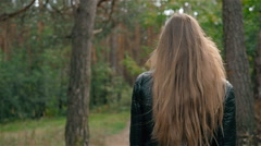 Outdoor fashion shot of young beautiful lady in a forest, smiling girl on a walk Stock Footage