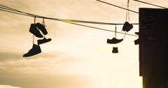 Closeup of sneakers hanging on a telephone wire - 4k Stock Footage