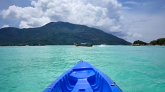 Floating in a kayak on  turquoise waters while a tail boat passes by Stock Footage