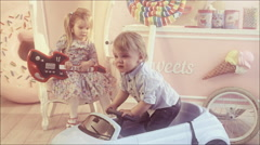Kids playing in the children's room with children's machine and with a guitar. Stock Footage