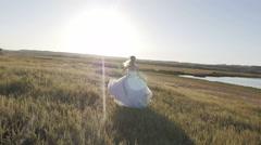 Bride running across the field to meet the sun at sunset Arkistovideo