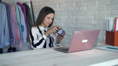 Young businesswoman playing game on smartphone sitting by table in office Stock Footage