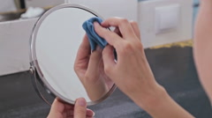 Woman cleaning mirror at home Stock Footage