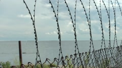 Sea behind barbed wire fences Stock Footage