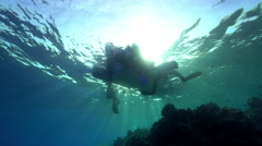 Scuba divers around a dive boat at sunlight - underwater view Stock Footage