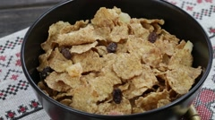 Cereal flakes pour yogurt and stirred . Crunchy tasty muesli food background Stock Footage