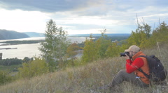 Hiking man with a backpack photographed on a photo camera natural autumn land Stock Footage