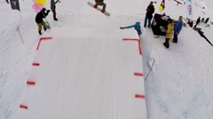 Quadrocopter shoot snowboarder jump over springboard. Ski resort. People riding Stock Footage