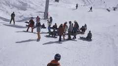 Ski resort. Snowboarders on slope. Preparing for ride. White mountain. Sunny day Stock Footage