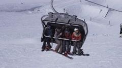 Ski resort. Snowboarders ride on ski lift. Landscape of snowy mountains. Uniform Stock Footage