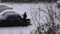 Man removes snow from car with brush on parking place Stock Footage
