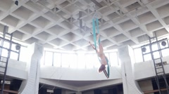 Aerial gymnast proceeds to circus and performs the splits in the air Stock Footage