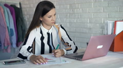 Young businesswoman writing notes in documents sitting by desk at office Stock Footage