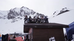 Ski resort. Snowboarders sitting on roof of house in encamp. Skiers. Mountains Stock Footage