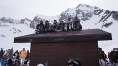 Ski resort. Snowboarders sitting on roof of house in encamp. Wave hand in camera Stock Footage