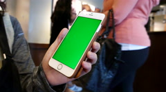 Hand holding green screen iphone inside Starbucks store with 4k resolution. Stock Footage