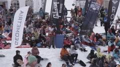 Ski resort. Snowboarders and skiers watching in encamp. Having rest. Cameraman Stock Footage