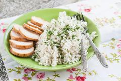 White rice with greens and sliced pieces of meat grilled on a green plate Stock Photos