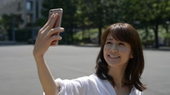 Japanese girl with her smartphone making a selfie Stock Footage