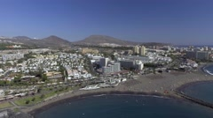 Buildings and beach of Playa de Las Americas, aerial view of Tenerife coastline Stock Footage
