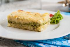 Potato casserole with spinach on a plate and cutlery Stock Photos