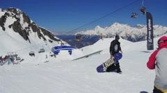 Snowboarder slide on rail, flip. Sunny day. Ski resort. Mountains. Extreme sport Stock Footage
