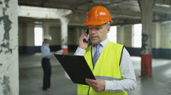 4K Engineer or architect talking on phone at construction site Stock Footage