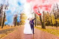 Wedding couple with color smoke in the autumn park. Colour bomb Stock Photos