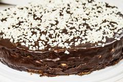Round chocolate cake sprinkled with white chocolate grit Stock Photos
