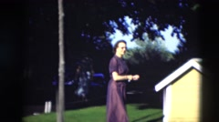 1951: well dressed people gathering in yard in front of a yellow dog house Stock Footage