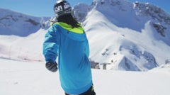 Skier back slide on slope. Sunny day. Ski resort. Snowy mountains. Extreme sport Stock Footage