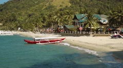 Red outrigger boat on clean white sand beach with a beautiful house, Philippines Stock Footage