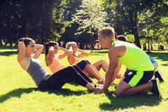 Group of friends or sportsmen exercising outdoors Stock Photos