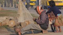 Man repairing net, kids playing,Chitwan,National Park,Nepal Stock Footage