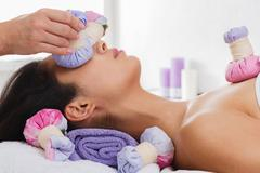Woman has herbal ball massage in ayurveda spa wellness center Stock Photos