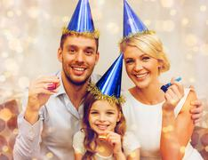 Smiling family in blue hats blowing favor horns Stock Photos