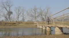 Man walking over bamboo bridge,Chitwan,National Park,Nepal Stock Footage