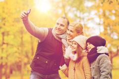 Happy family with camera in autumn park Stock Photos