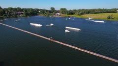 People riding on wakeboard on pond aerial view. Stock Footage